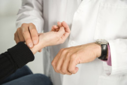 Doctor taking patient's pulse