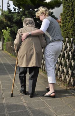 Senior woman walks with assistance of cane and caring helper