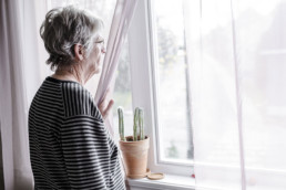 Senior woman in memory care looks out the window
