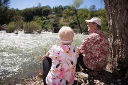 Close senior friends sitting by a stream