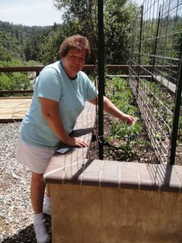 Senior woman tending to the raised bed garden