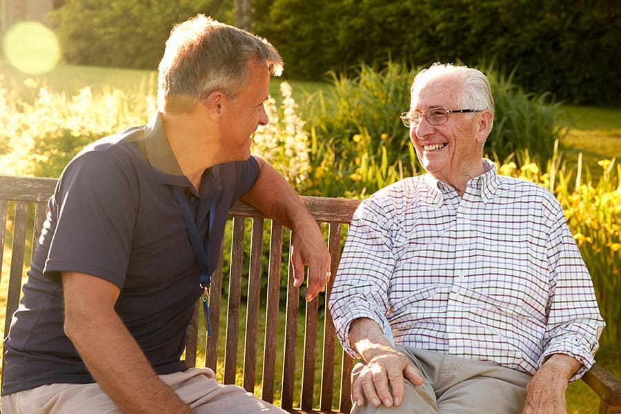 two men talking on bench
