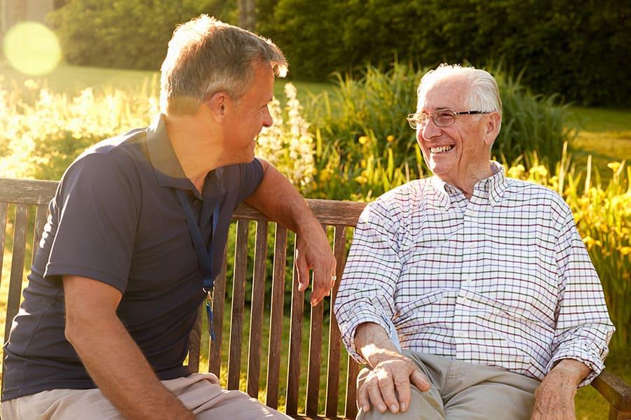 men talking on bench